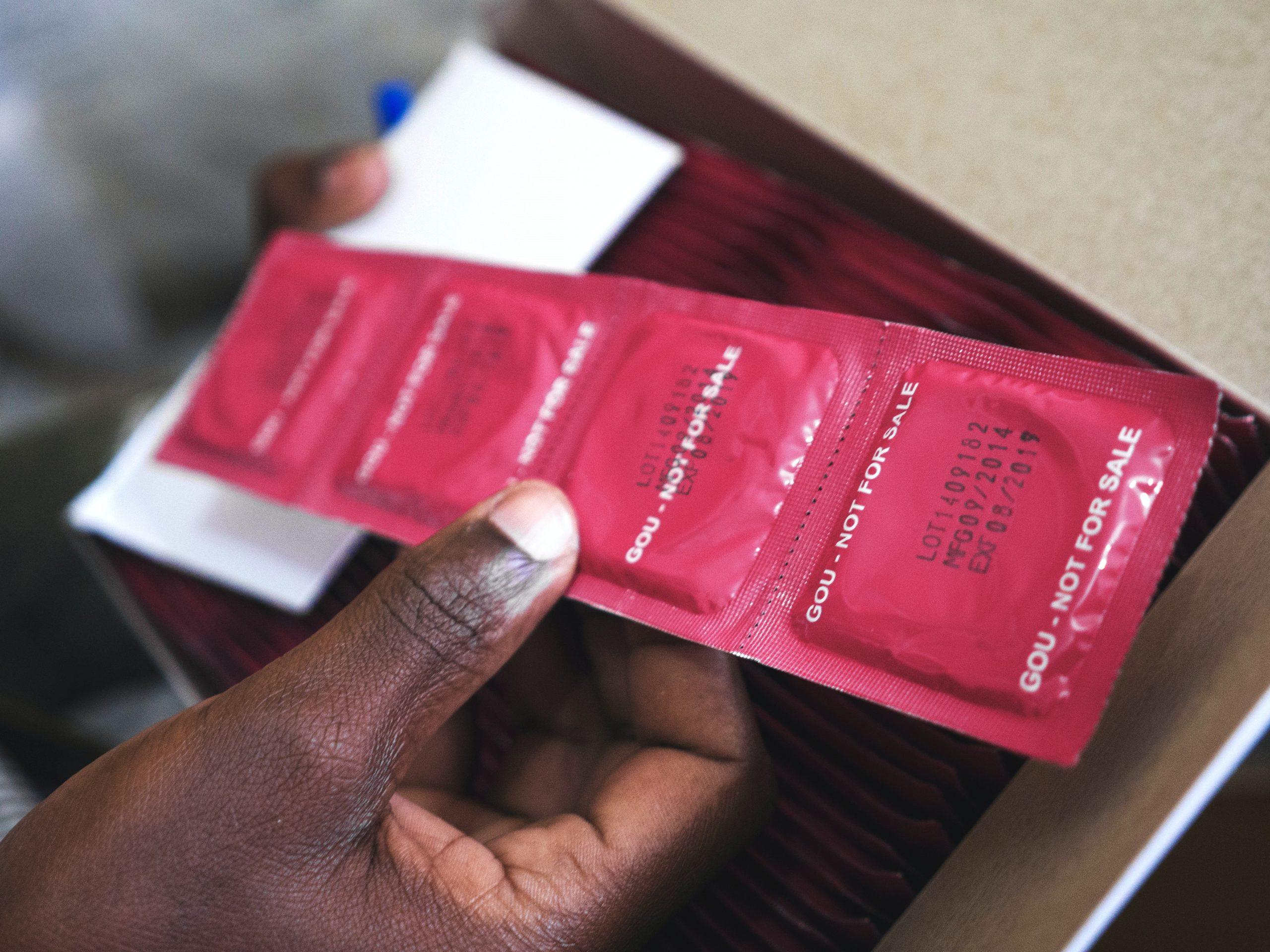 man holding red condom packs